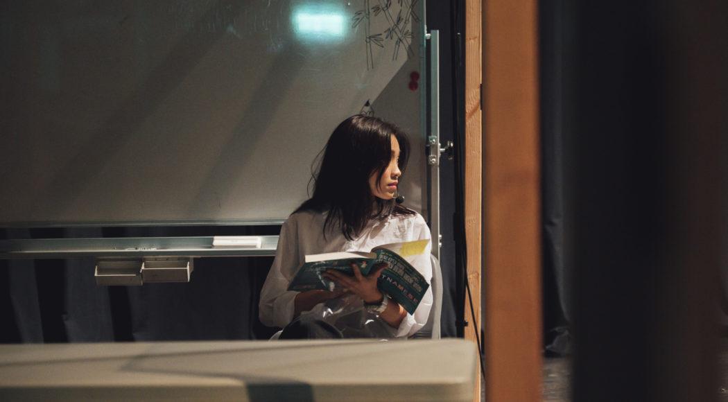 Eine vietnamesische Frau sitzt frontal an einem Tisch neben einem großen Fenster. Sie hält ein aufgeschlagenes Magazin in der Hand. sie schaut dabei nach rechts aus dem Fenster. Hinter ihr leuchtet ein grünes Exist-Schild. Der Fensterrahmen ist orange.