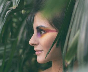 Das Foto von Ivo Saint im Querformat zeigt einen Ausschnitt des Profils der amerikanischen Künstlerin Michaela Rea Catranis. Das Gesicht der Komponistin ist mittig im Bild und im Mittelgrund, es ist vom Kinn bis zum Haaransatz in einer Nahaufnahme abgebildet. Im Hintergrund erkennt man unscharf dunkelgrüne Pflanzenteile, die die linke Seite füllen. Auf der rechten Seite des Gesichts, das Ohr bedeckend befinden sich ähnliche Pflanzenteile im Vordergrund, welche teilweise auch unscharf sind. Catranis hat ihren Blick nach links aus dem Foto hinaus gewandt, sodass nur die linke Gesichtshälfte zu sehen ist. Sie hat dunkelbraunes Haar, dunkle Brauen und Augen und helle Haut. Ihre Lippen sind zart rosig und die Augen auffällig in Lila-, Rot- und Orangetönen geschminkt, was besonders zum großflächigen dunklen Grün in Kontrast steht.